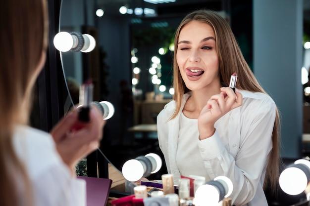 Vrouw met lippenstift spiegel kijken Gratis Foto