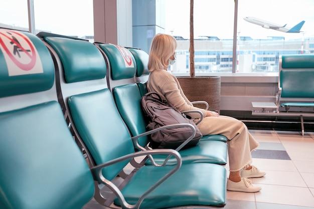 Vrouw met masker kijkt door raam en zit sociale stoel op afstand op de luchthaven. reizen vakantie zakenreis concept. selectieve aandacht. Premium Foto