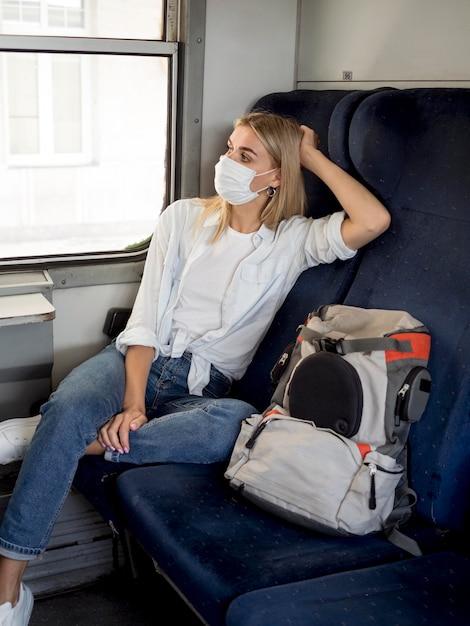 Vrouw met masker reizen met de trein Gratis Foto