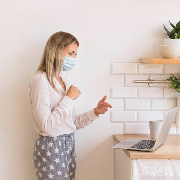 Vrouw met masker thuis werken Gratis Foto