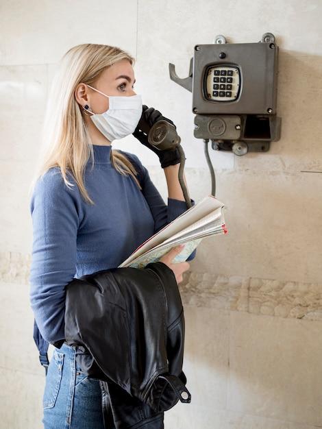 Vrouw met masker via telefoon Gratis Foto