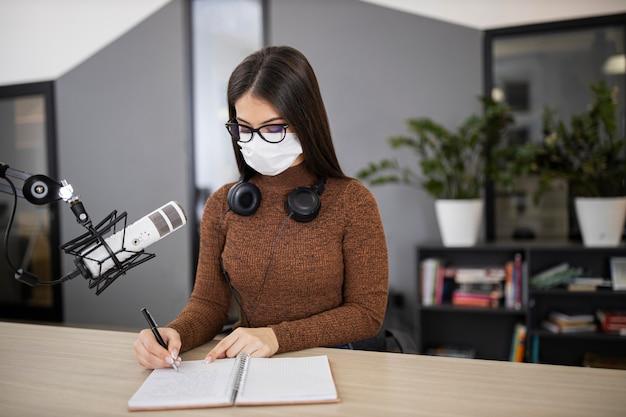 Vrouw met medisch masker op de radio met microfoon en notitieboekje Gratis Foto