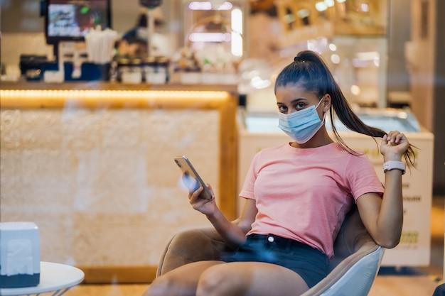 Vrouw met medische gezichtsmasker met smartphone in café. Gratis Foto