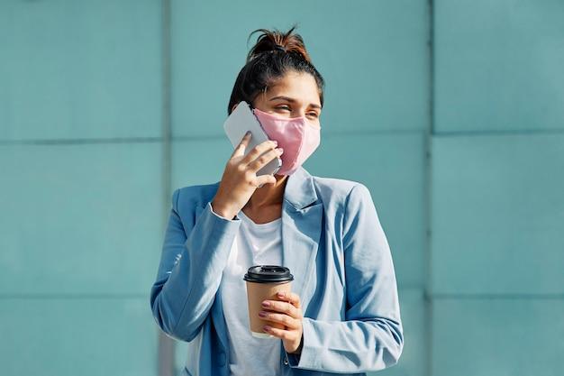 Vrouw met medische masker en koffie praten over smartphone op de luchthaven tijdens pandemie Gratis Foto