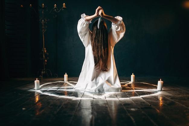 Vrouw met mes in handen die in pentagramcirkel met kaarsen zitten. donker magisch ritueel, occultisme en exorcisme, bovennatuurlijke kracht Premium Foto