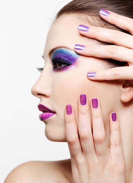 Vrouw met mooi gezicht en manierstijlsamenstelling en schoonheids purpere manicure van vingernagels Gratis Foto