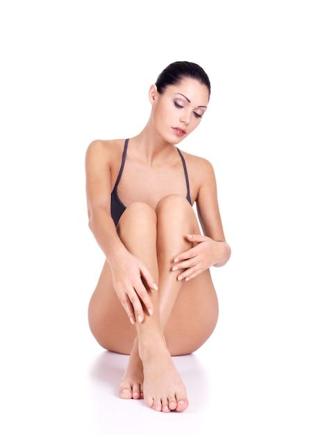 Vrouw met mooie benen in bikini zit op witte achtergrond Gratis Foto