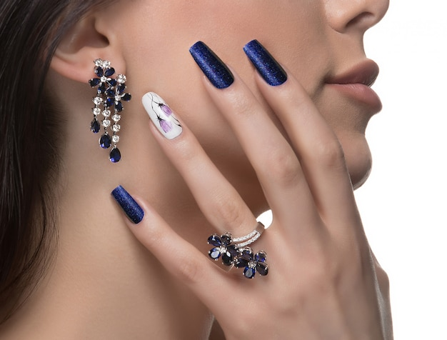 Vrouw met nagelkunst die de oorringen en de ring van de ontwerpluxe bevorderen. Gratis Foto