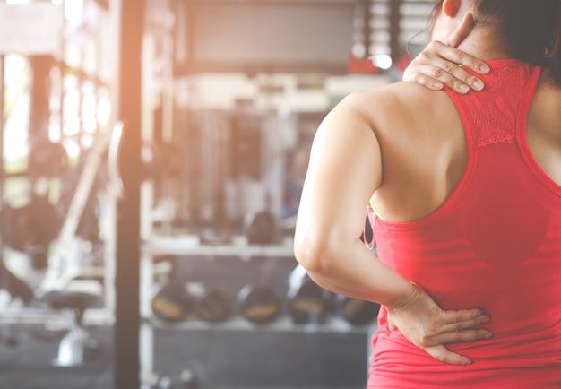 Vrouw met nekpijn, massage van vrouwelijk lichaam. Premium Foto