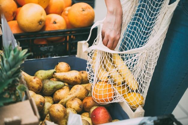 Vrouw met netzakhoogtepunt van verse groenten die bij de opslag, nul afvalconcept winkelen Premium Foto