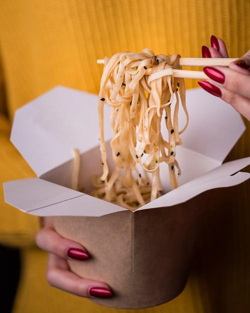 Vrouw met noedels in eetstokjes Gratis Foto