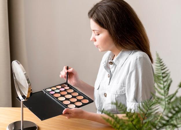 Vrouw met oogschaduwpalet Gratis Foto