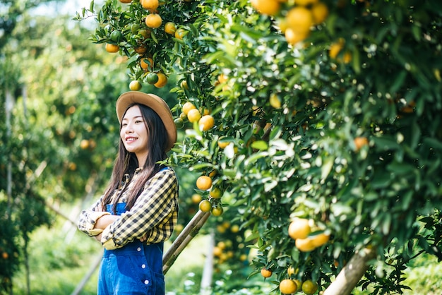 Vrouw met oranje plantage Gratis Foto