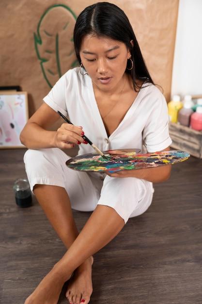 Vrouw met palet en schilderij penseel Gratis Foto
