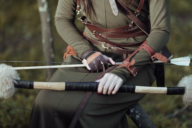 Vrouw met pijlen en boog zit op een omgevallen boom, close-up Premium Foto