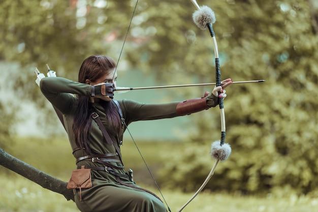 Vrouw met pijlen en boog zit op een omgevallen boom en richt op een doelwit Premium Foto