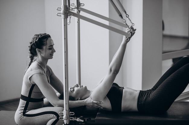 Vrouw met pilates trainer beoefenen van pilates Gratis Foto