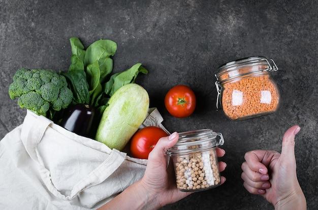 Vrouw met pot met kikkererwten. groenten, herbruikbare tas. glazen pot - linzen. geen afvalconcept Premium Foto