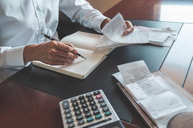 Vrouw met rekeningen en calculator. vrouw die calculator gebruiken om rekeningen te berekenen bij de lijst in bureau. Premium Foto