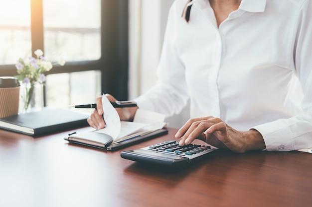 Vrouw met rekeningen en calculator. vrouw die calculator gebruikt om rekeningen bij de lijst in bureau te berekenen. Premium Foto