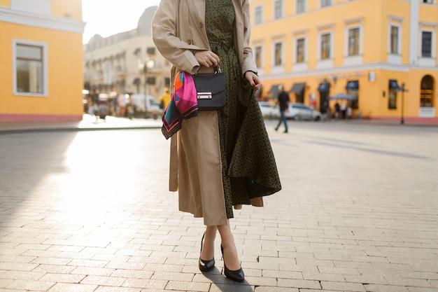 Vrouw met rode haren en lichte make-up op straat lopen. beige jas en groene jurk dragen. Gratis Foto