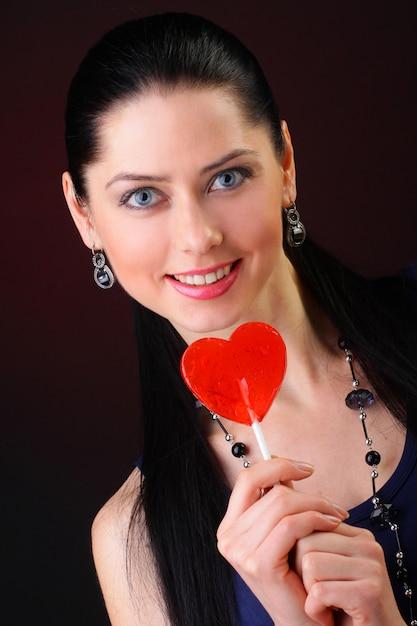 Vrouw met rode hartvormige lolly Premium Foto