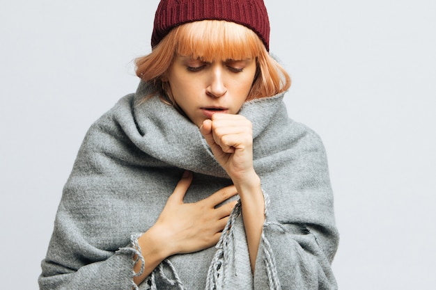 Vrouw met rode hoed hoesten, voelt de eerste symptomen van ziekte. bronchitis, Premium Foto