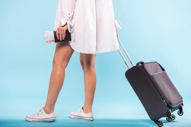 Vrouw met rollende koffer en kaartjes Gratis Foto
