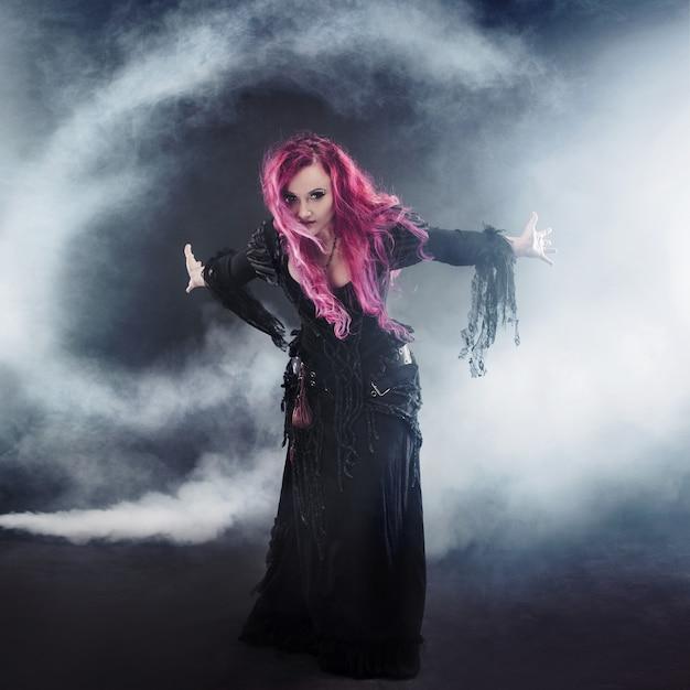 Vrouw met rood haar in heksen kostuum staande armen, sterke wind Premium Foto