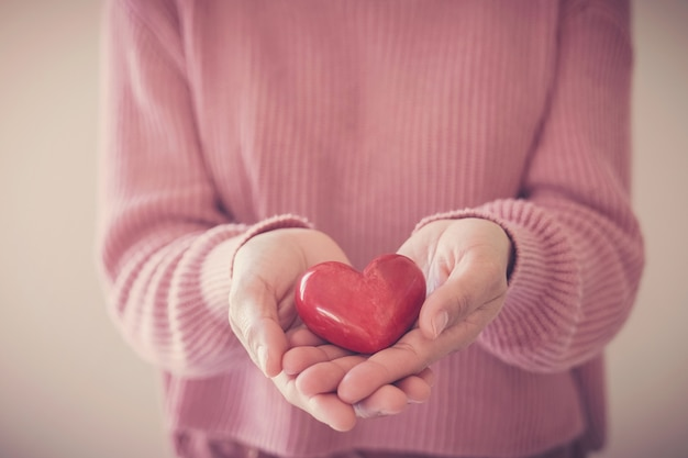 Vrouw met rood hart, ziektekostenverzekering, donatieconcept, werelddag voor geestelijke gezondheid, wereldhartdag Premium Foto