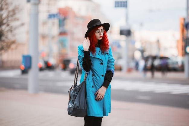 Vrouw met rood krullend haar in blauwe jas en zwarte ronde glazen van grote stad. Premium Foto