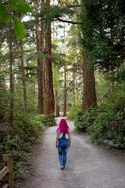 Vrouw met roze haren wandelen door het pad in het bos Gratis Foto