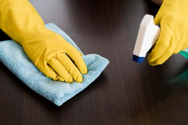 Vrouw met rubberhandschoenen die de lijst schoonmaken Gratis Foto