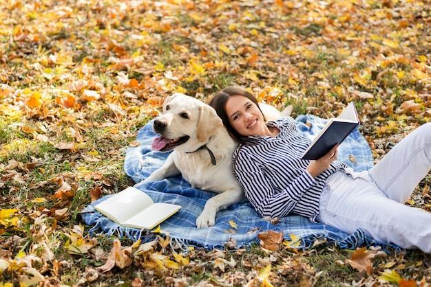 Vrouw met schattige hond zittend op een deken Gratis Foto