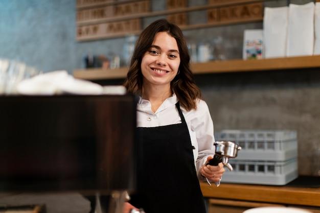 Vrouw met schort het stellen met de component van de koffiemachine Gratis Foto