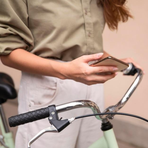 Vrouw met smartphone buitenshuis met fiets Gratis Foto