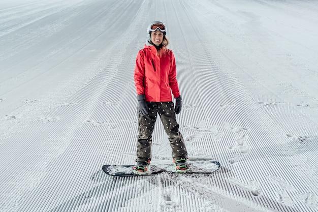 Vrouw met snowboard op de skipiste. 's avonds rijden Premium Foto