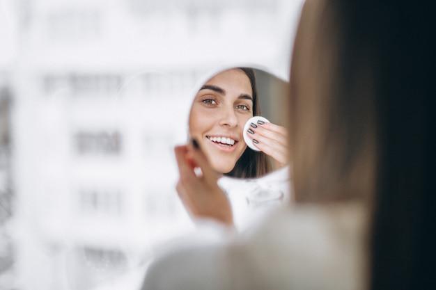 Vrouw met spiegel die make-up met stootkussen verwijdert Gratis Foto