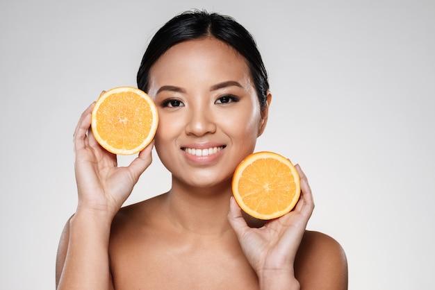 Vrouw met stukjes sinaasappel in de buurt van haar gezicht Gratis Foto