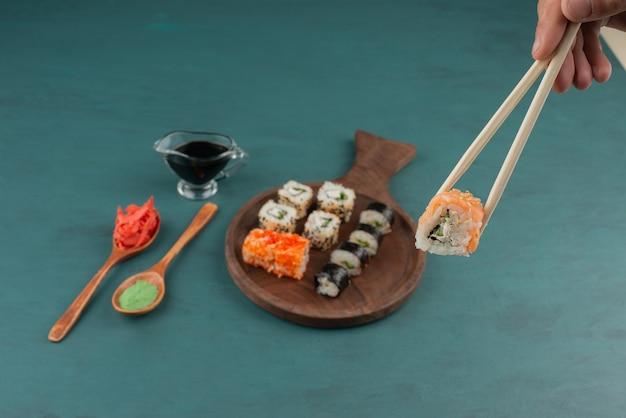 Vrouw met sushi roll met stokjes op blauwe tafel met ingelegde gember en sojasaus. Gratis Foto