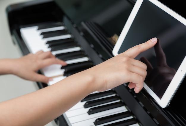 Vrouw met tablet leren om de piano te spelen Gratis Foto