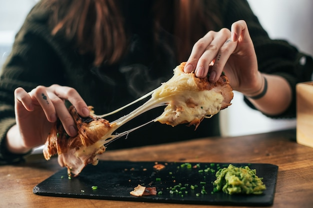Vrouw met tatoeages op vingers breekt klaar om croissant met gesmolten kaas en ham te eten Gratis Foto