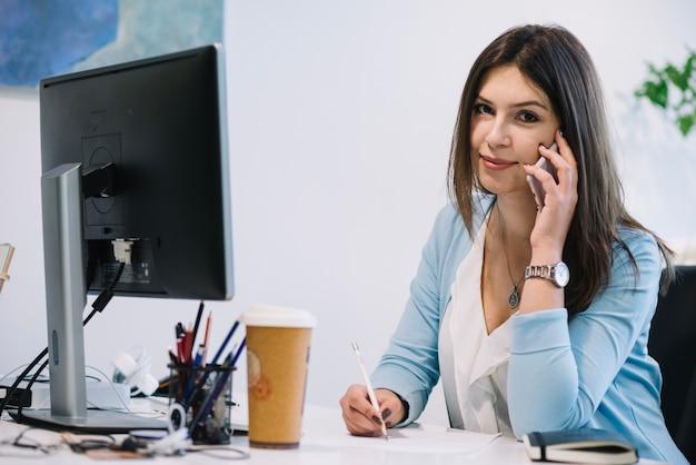Vrouw met telefoon en camera kijken Gratis Foto