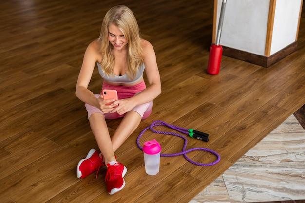 Vrouw met telefoon en springtouw Gratis Foto