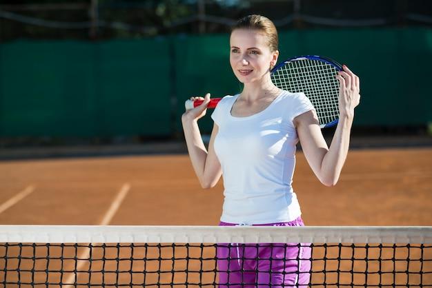 Vrouw met tennisracket op de rug Gratis Foto
