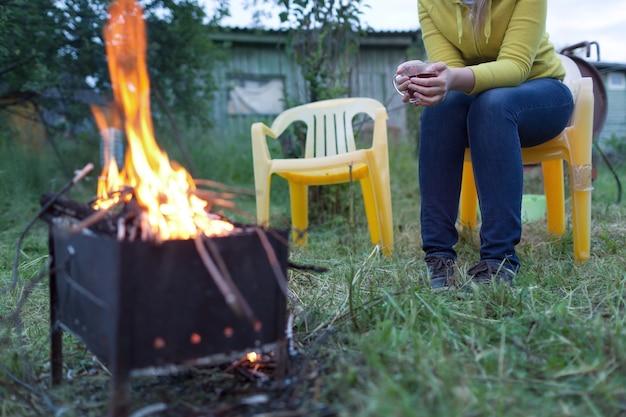Vrouw met thee dichtbij het vuur in de tuin foto premium download