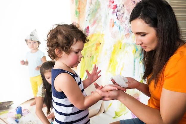 Vrouw met twee baby's schilderen met verf en borstels zittend aan kindertafel, kleurrijk oppervlak Premium Foto
