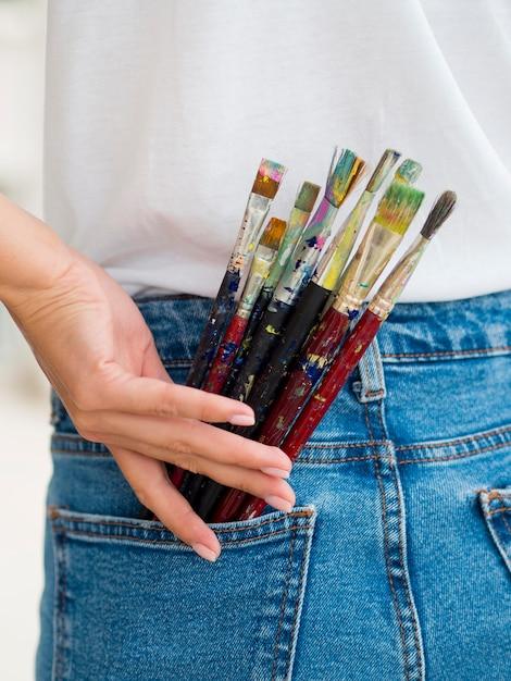 Vrouw met verfborstels in achterzak Gratis Foto