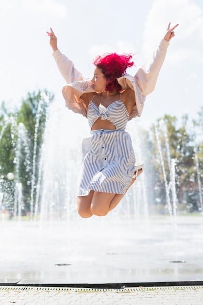 Vrouw met waterfontein op achtergrond Gratis Foto