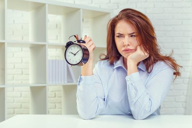 Vrouw met wekker aan tafel op kantoor Premium Foto